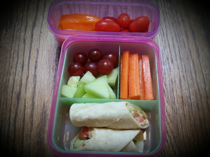 Hummus & veggie roll-up with fruit and carrot sticks, and pepper & grape tomato snack